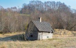 Старое здание разваливаясь бани в поле на ферме в Латвии стоковое фото