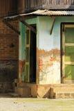 Старое зеленое здание, цемент заштукатуренный для того чтобы увидеть кирпич стоковое фото