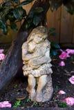 Старое каменное scupture девушки держа кота под кустом camelia Стоковое Изображение RF