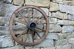 Старое колесо смертной казни через повешение фуры на стене сделанной камней стоковое изображение