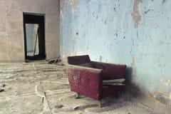 Старое красное кресло напротив черного входа в разрушенной комнате в Чернобыль, зоне отчуждения Pripyat, Украины Стоковая Фотография RF