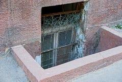 Старое окно за барами в подвале на стене тротуаром стоковые изображения rf
