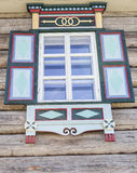Старое окно с с ярко покрашенными штарками стеклянными с голубым небом на предпосылке деревянной стены журнала h сельской местнос Стоковые Изображения RF