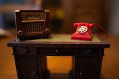 Старое радио кукольного домика и красный телефон стоковые фотографии rf