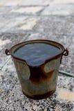 Старое ржавое ведро металла заполненное с водой стоковые фото
