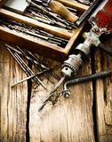 Старое сверло, коробка с сверлами на деревянной предпосылке Стоковое Изображение