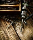 Старое сверло, коробка с сверлами на деревянной предпосылке Стоковая Фотография RF