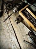 Старое сверло, коробка с сверлами, плоскогубцы и правитель дальше Стоковое Изображение RF