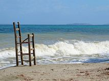 Старое сломанное деревянное barstool на пляже и море на заднем плане стоковое фото rf