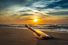 Старое сообщение в бутылке на береге моря стоковые фотографии rf