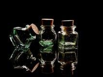 Старое хранение зеленого стекла раздражает, баки, подсвеченные на черноте Стоковые Изображения RF