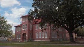 Старое школьное здание кирпича с спортивной площадкой и школьными автобусами, 4K сток-видео