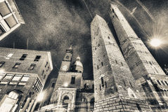 Старое Asinelli возвышается на ноче с церковью в болонья, Италии Стоковые Изображения RF