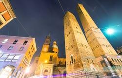 Старое Asinelli возвышается на ноче с церковью в болонья, Италии Стоковые Фотографии RF