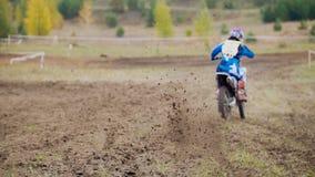 Старт гонщика Motocross ехать его велосипед MX креста грязи - вид сзади Стоковая Фотография