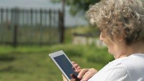 Старуха держит серебряную таблетку компьютера outdoors видеоматериал