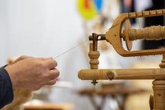 старуха используя колесо старых шерстей закручивая Стоковая Фотография RF