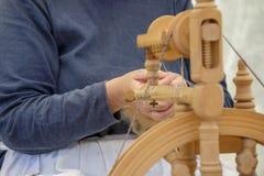 старуха используя колесо старых шерстей закручивая Стоковая Фотография
