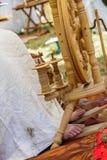 старуха используя колесо старых шерстей закручивая Стоковое Изображение