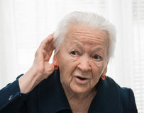 Старуха кладя руку к ее уху. Плохой слух стоковые фотографии rf