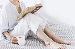 Старуха на кровати читая старую книгу с чашкой чая лимона стоковые фото