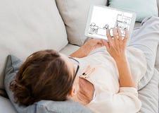 старуха на софе при таблетка смотря новый дизайн s для дома Стоковое Фото