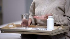 Старуха принимая таблетки в медицинском центре, страдая от проблемы здоровья, заболевание стоковая фотография rf