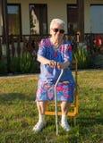 Старуха сидя на стуле с тросточкой Стоковые Изображения