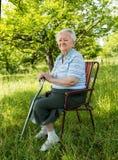 Старуха сидя на стуле Стоковое Изображение