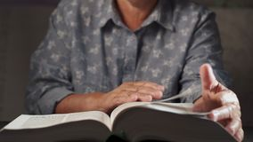 Старуха слегка ударяя через страницы книги Бабушка с библией Сконцентрированный пожилой пенсионер с морщинками на руках акции видеоматериалы