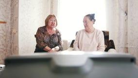 2 старухи смотря ТВ и говоря друг к другу акции видеоматериалы