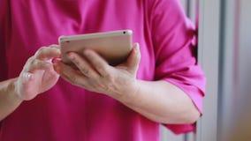 Старшая азиатская женщина используя планшет в живя комнате видеоматериал