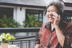 Старшая беседа женщины на мобильном телефоне в кафе пожилое женское speakin Стоковая Фотография RF