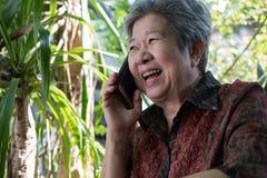 Старшая беседа женщины на мобильном телефоне в саде пожилая женщина говорит Стоковая Фотография