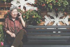 Старшая беседа женщины на мобильном телефоне в саде пожилая женщина говорит Стоковое Изображение