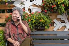 Старшая беседа женщины на мобильном телефоне в саде пожилая женщина говорит Стоковые Изображения