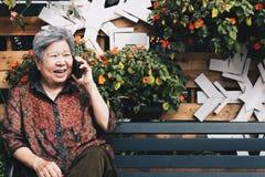 Старшая беседа женщины на мобильном телефоне в саде пожилая женщина говорит Стоковая Фотография RF