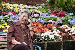 Старшая беседа женщины на мобильном телефоне в саде пожилая женщина говорит Стоковое Фото