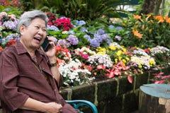 Старшая беседа женщины на мобильном телефоне в саде пожилая женщина говорит Стоковые Фото