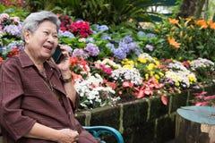 Старшая беседа женщины на мобильном телефоне в саде пожилая женщина говорит Стоковое Изображение RF