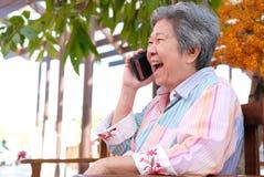 Старшая беседа женщины на мобильном телефоне в саде пожилая женщина говорит Стоковое фото RF
