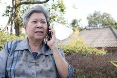 Старшая беседа женщины на мобильном телефоне пока сидящ на стенде в garde Стоковые Фото