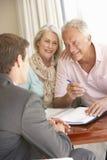 Старшая встреча пар с финансовым советником дома стоковые фотографии rf
