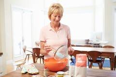 Старшая выпечка женщины в кухне Стоковое фото RF