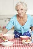 Старшая выпечка женщины в кухне Стоковая Фотография RF