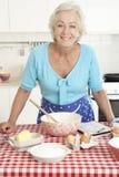 Старшая выпечка женщины в кухне Стоковое Изображение