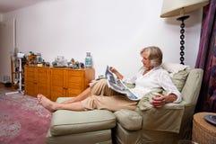 Старшая газета чтения женщины пока ослабляющ на кресле дома Стоковые Изображения