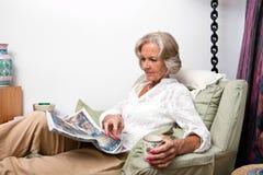 Старшая газета чтения женщины пока ослабляющ дома Стоковое фото RF