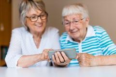 Старшая дама используя умный телефон с ее матерью стоковые фото
