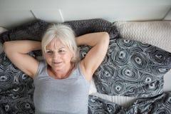 Старшая дама лежа в мечтать кровати стоковые фотографии rf